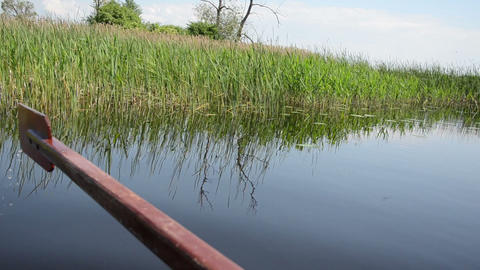 boat floats on lake along long the water green bulrush Footage