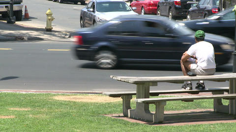 A man sitting on a picnic bench watching traffic Live Action