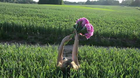 woman lies down the green young corn with peonies back view Footage