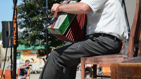 senior man plays with small accordion with foot hitting throb Footage