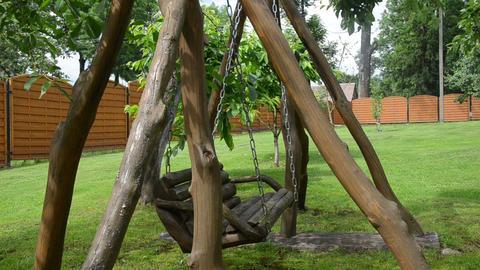 closeup of empty wooden swing on chain sway in backyard garden Footage