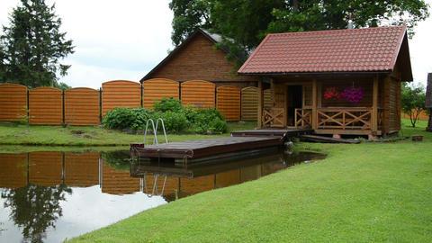 Garden wooden log bath bathhouse sauna near small bridge on pond Footage