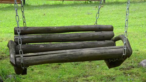 empty wooden swing on chain sway in backyard garden Footage