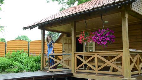 Girl walk small wooden gates near rural wooden log house Footage