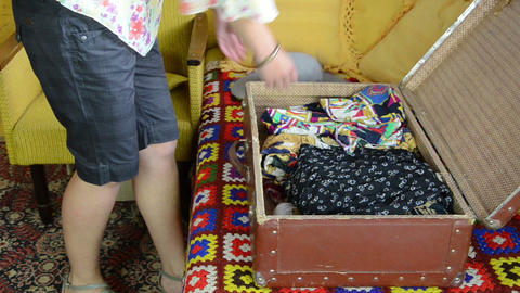 Woman unpack her clothes from old travelling port trunk bag Footage