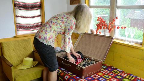 Blond woman girl unpack her clothes into retro travel suitcase Footage