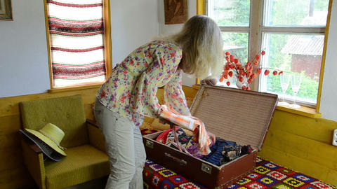 woman arrive in rural villa with suitcase take out summer shirt Footage