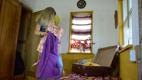 girl chooses between two different blouses packed suitcase Footage
