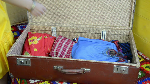 hand finish packing suitcase puts clothes takes the yellow hat Footage