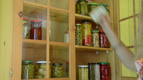 Girl put glass pots with canned pickled food product to shelf Footage
