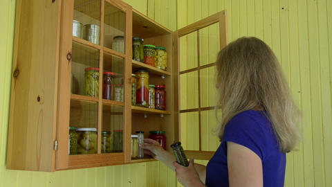 Girl open food rack put few jars with canned organic products Footage