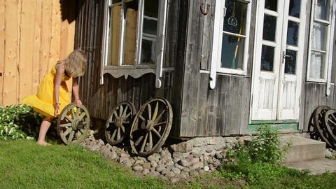 Woman in yellow dress rolls old carriage wheel near rural house Footage
