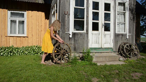 Lady in yellow dress rolls old carriage wheel near rural house Footage