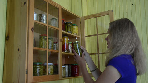 Lady take glass jar with canned olive and mushrooms from cabinet Footage