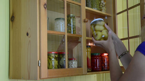 girl from kitchen cupboards inspect jar of canned tomato Footage