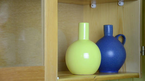 hand puts on wooden shelf a nice clay vases side by side Live Action