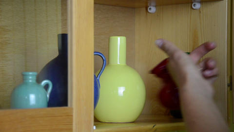 Woman hand take small colorful crockery vases from wall cabinet Footage