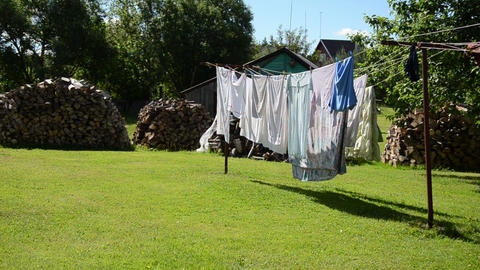 laundry dry on outdoor rope move in wind and firewood stacked Footage