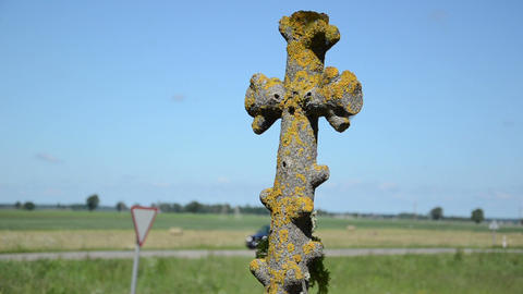 Retro Mossy Stone Cross Closeup And Car Drive On Background stock footage