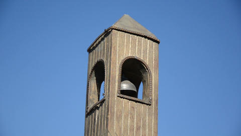 Wooden belfry imitation with bell move on background of blue sky Footage