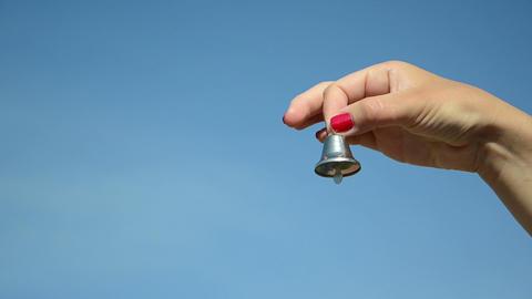 hand shake jingle small silver bell on blue sky Footage