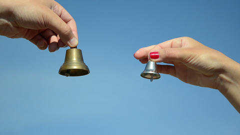 boy and girl hands jingle with silver bronze bell on blue sky Footage