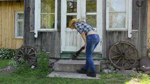 Worker woman clean sweep stairs with wooden broom in rural yard Footage