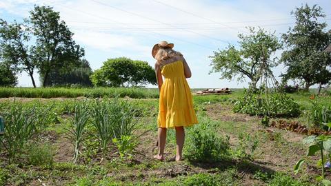 Barefoot gardener woman in yellow dress and hat work in garden Footage