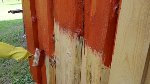 hand glove painting wooden plank house wall with brush red color Footage