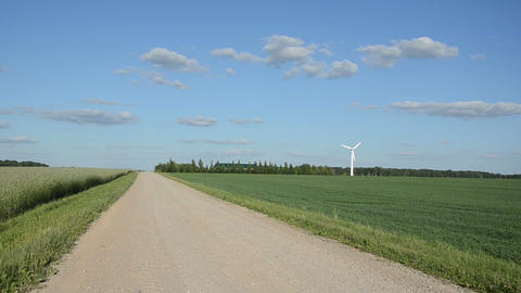 Rural gravel road between fields and wind mill windmill rotate Footage