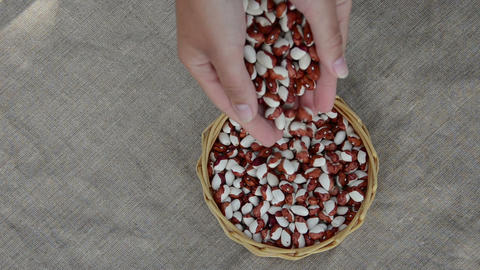 Hands pour decorative multicolor beans to wicker dish Footage