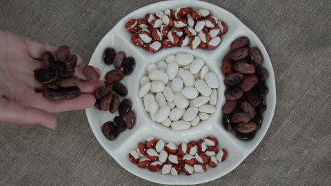 Hands pour various species kind multicolor beans to white dish Footage