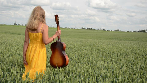 through green corn goes girl with yellow dress guitar in hand Footage