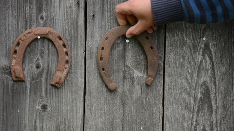 hand hanging wall three iron horseshoes on hammered nail Footage