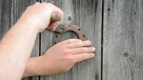 man hand with hammer take horse shoe symbol of luck wood wall Footage