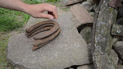 hand puts rusty iron horseshoes on a flat stone Footage