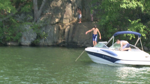 Children jumping off a moored motor boat and swinging on a rope off a cliff Footage