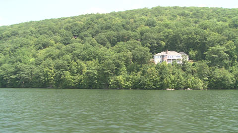 Large house nestled in trees along the water Footage