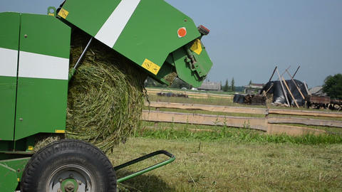 cut grass equipment turns the cut green grass in large bales Live Action