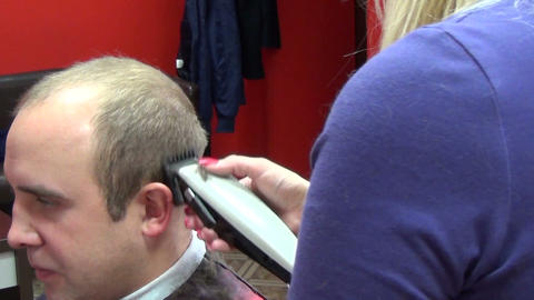 Hairdresser woman shave man client hair trimmer in barber shop Footage