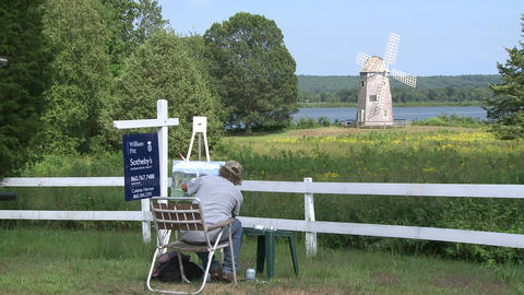 Artist painting windmill by the water (1 of 2) Footage
