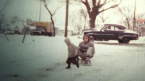 1958 - Kid Pulling Dad Around On Snow Sled Footage