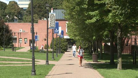 Students walking along walkway between University buildings Footage