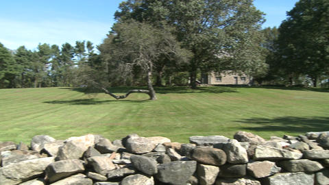 Stone wall around a home with grassy field and trees (2 of 2) Footage