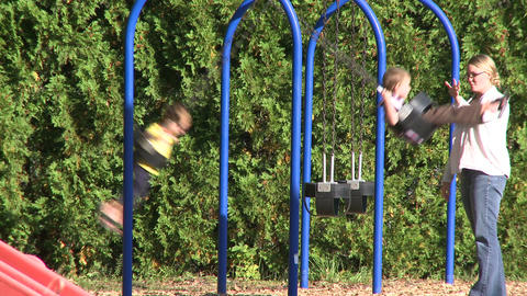Children swinging on swings at a small playground (4 of 5) Footage