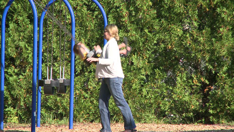 Children swinging on swings at a small playground (3 of 5) Footage