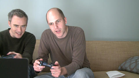 Two men playing a video game in the living room (4 of 5) Footage