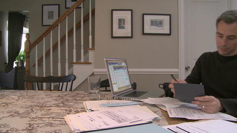 A man going over his bills on his dining room table (3 of 3) Footage