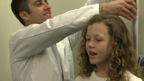 Doctor measures height of teenage patient (1 of 2) Footage