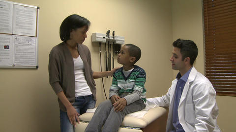 Concerned mom with her son at doctors office Footage